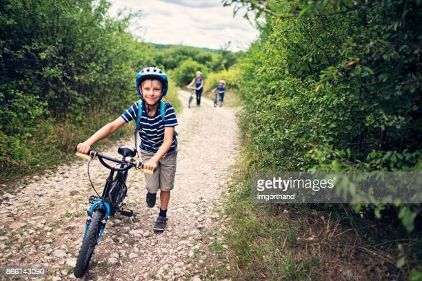 Family riding bicycles on dirt road