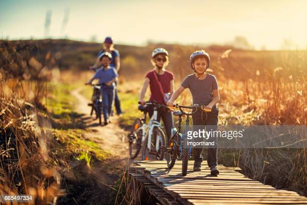 Family riding bicycles on early spring evening
