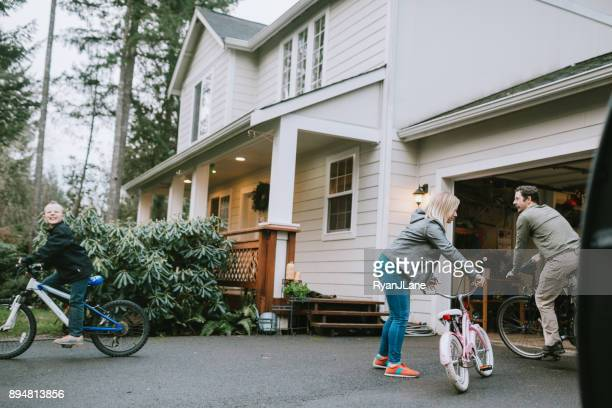family riding bikes in home driveway - noroeste do pacífico imagens e fotografias de stock