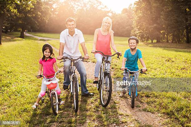 Family riding bikes in the park at sunset.