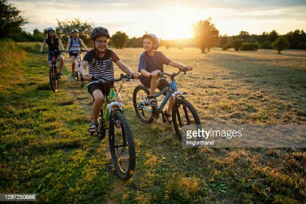 family riding bikes on sunny summer day - bicycle stock pictures, royalty-free photos & images