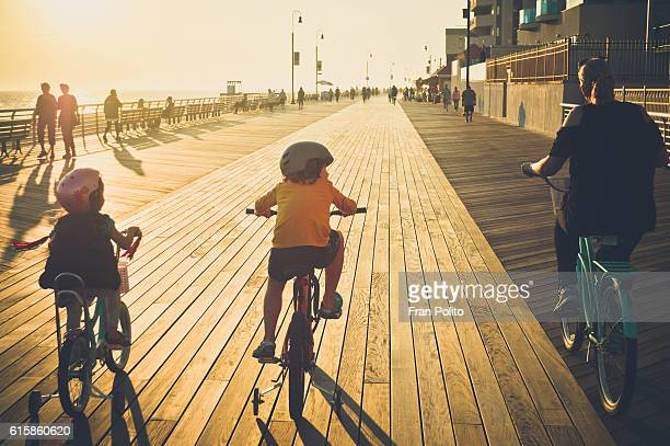Family riding bikes on the boardwalk at the beach.