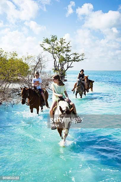 Family riding horses through water