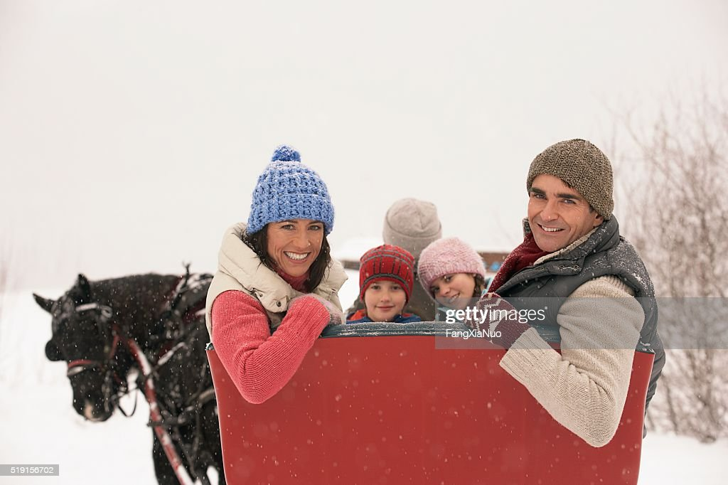 Family riding in horse drawn sleigh : Stock Photo