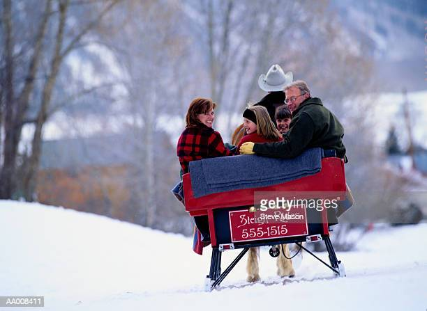 Family riding in sleigh, rear view