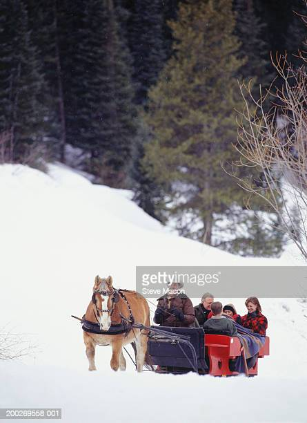 Family riding in sleigh up snow covered slope
