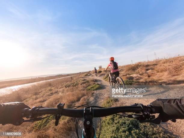 pov, family riding mountain bikes along single track shoreline trail - mountain view california stock pictures, royalty-free photos & images
