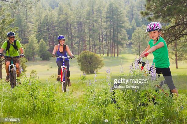 Family riding mountain bikes in meadow