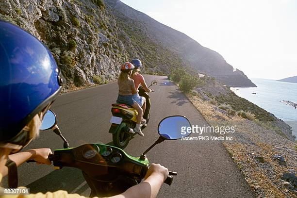 family riding scooters in kalymnos, greece - moped stock photos and pictures