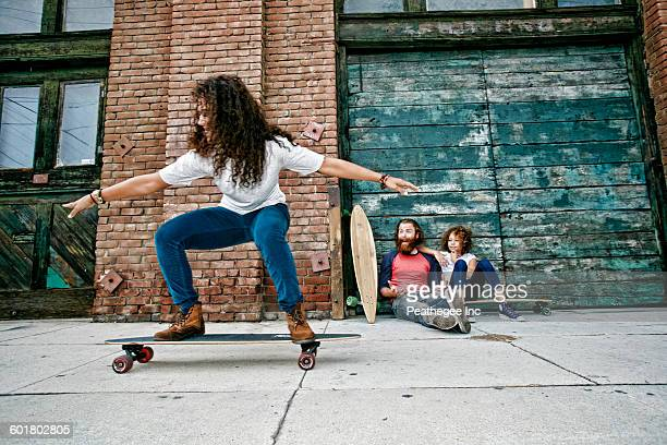 family riding skateboards on sidewalk - longboard skating stock pictures, royalty-free photos & images