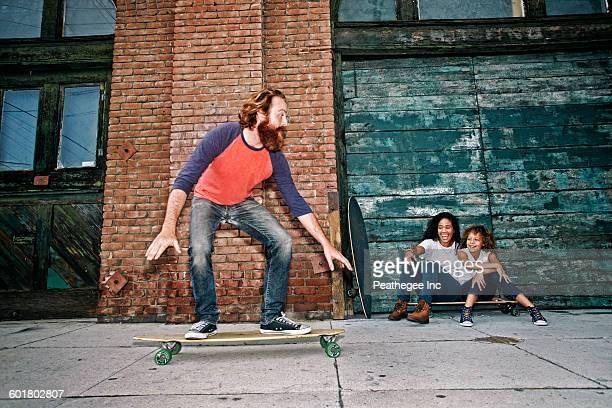family riding skateboards on sidewalk - longboard skating stock-fotos und bilder