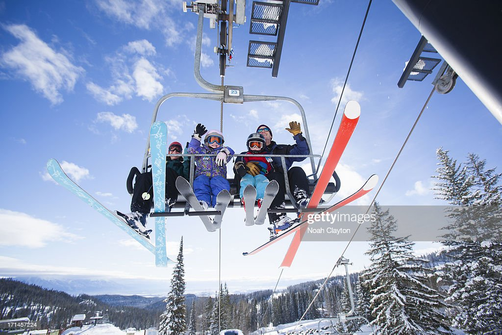 Charming Family Riding Ski Chairlift And Waving At Viewer