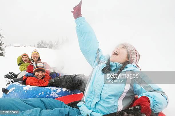 Family riding snow tubes