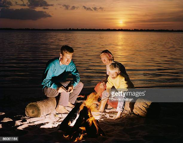 Family roasting hot-dogs by bonfire on the beach