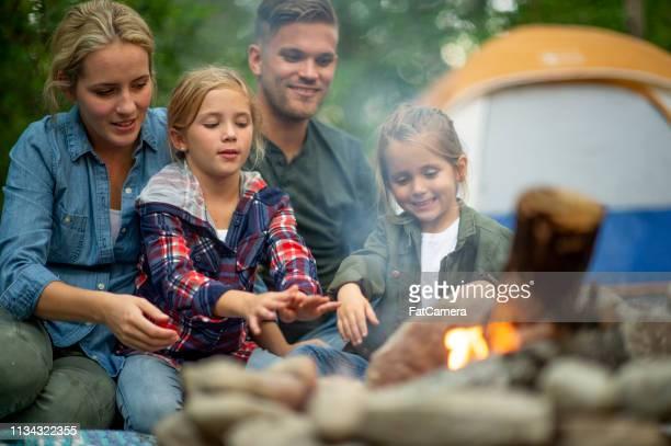 familiengröstung marshmallows auf dem campingplatz - holzfeuer stock-fotos und bilder