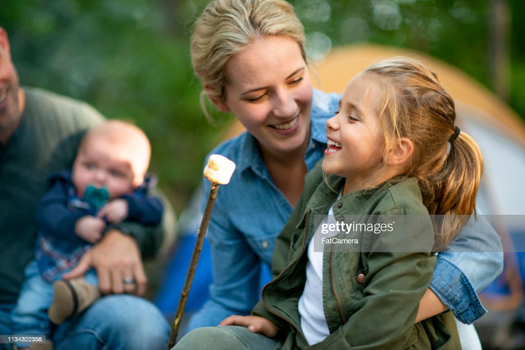 Family roasting marshmallows in campground : Stock Photo