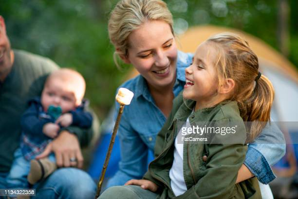 family roasting marshmallows in campground - camping stock photos and pictures