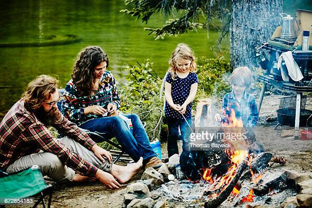 Family roasting marshmallows on campfire