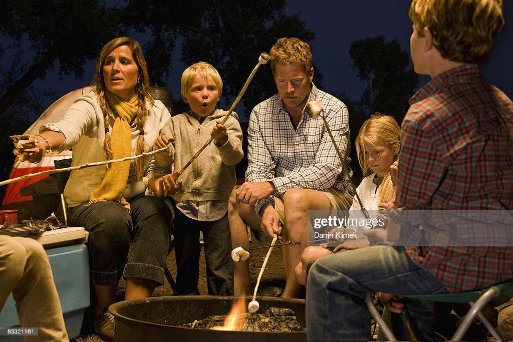 Family roasting marshmellows around campfire : Stock Photo