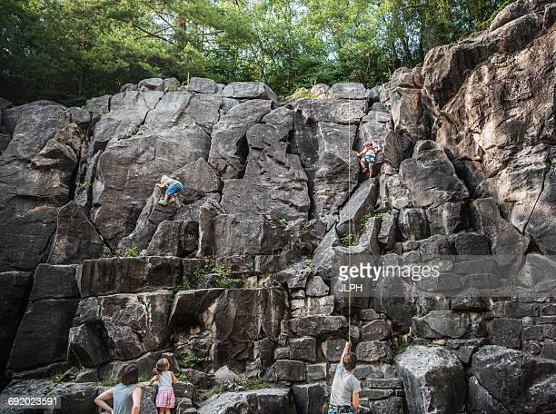Family rock climbing rock face