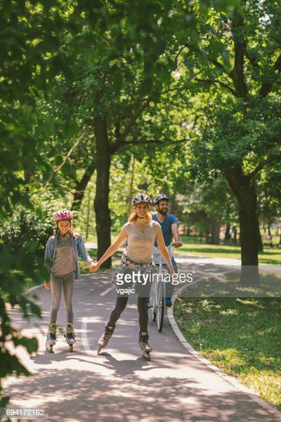 Family roller skating and riding bicycle