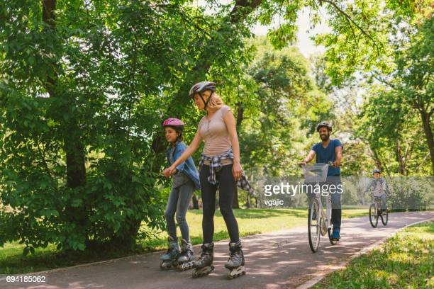 family roller skating and riding bicycle - inline skate stock photos and pictures