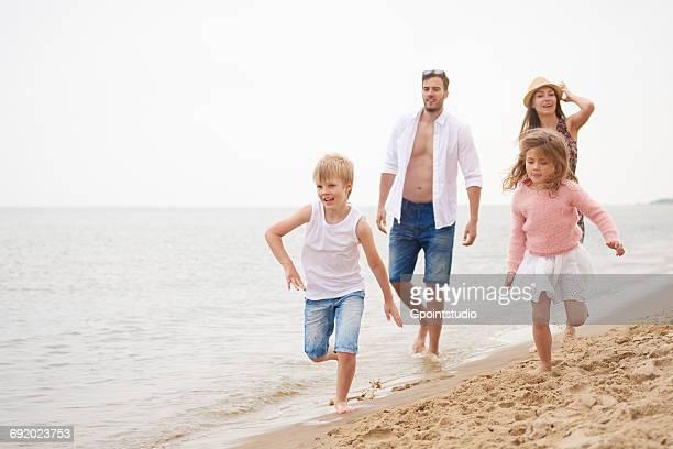 family running along sandy beach - helemaal losgeknoopt stockfoto's en -beelden