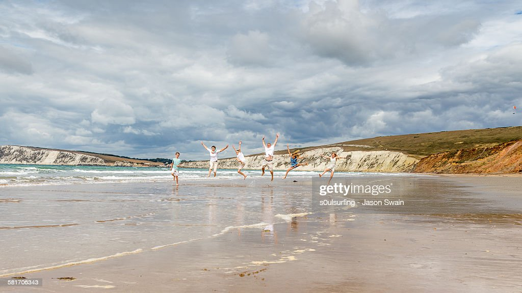Family running and jumping along the beach : Stock Photo