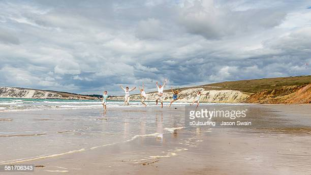 family running and jumping along the beach - s0ulsurfing stock pictures, royalty-free photos & images