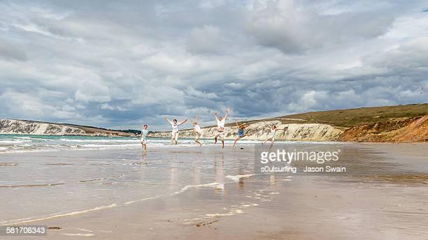 family running and jumping along the beach - s0ulsurfing stockfoto's en -beelden