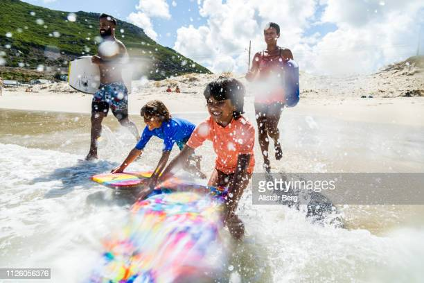 family running and splashing into sea together with body boards - vacanze foto e immagini stock