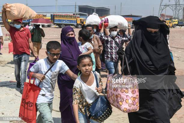 Family running at a ferry terminal trying to get on a ferry to travel home to celebrate Eid al-Fitr amid coronavirus crisis in Munshiganj on the...