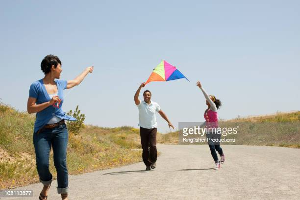 Family running down remote road flying kite together