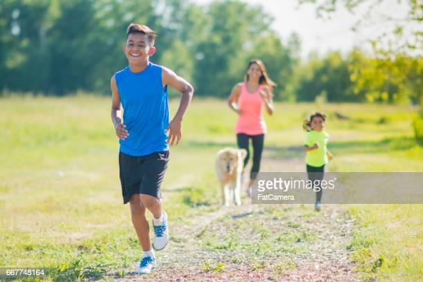 Family Running Following Son With Dog