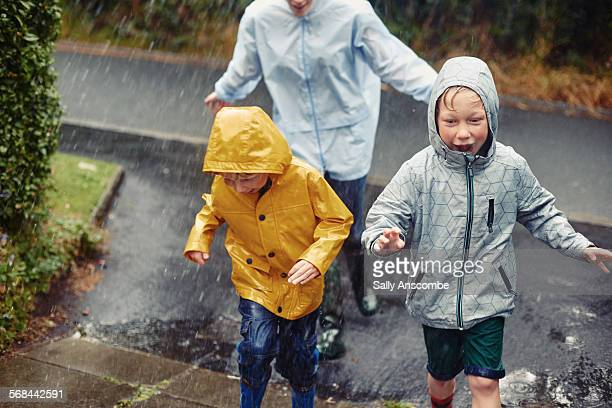 family running home in the rain - rain stock-fotos und bilder