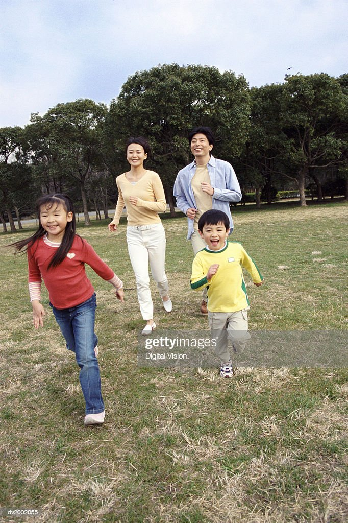 Family Running in a Park : Stock Photo