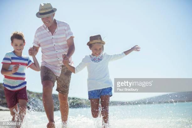 Family running in water on beach