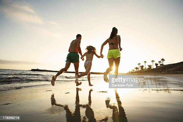 Family running on beach at sunset