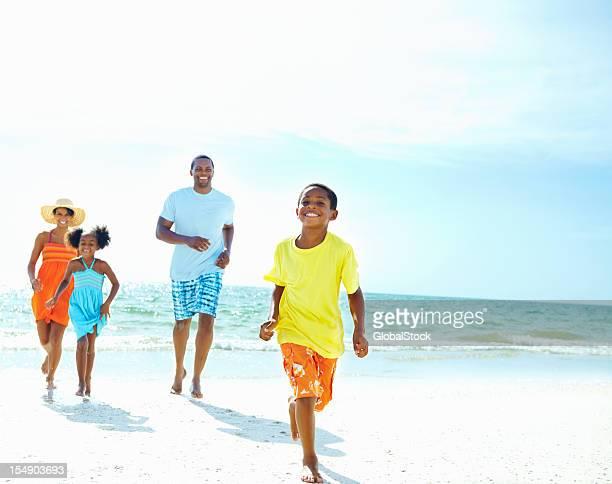 Family running on beach away from ocean