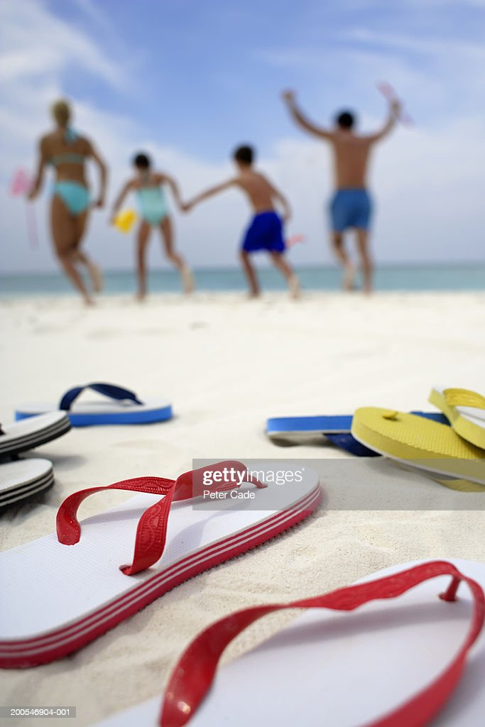 702d5ad73c6666 Family Running On Beach Focus On Flip Flops At Foreground Stock ...