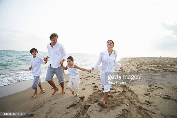 Family running on beach, parents holding children's (7-9) hands