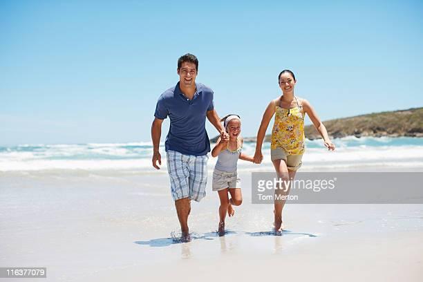 familie laufen am strand - familie mit einem kind stock-fotos und bilder