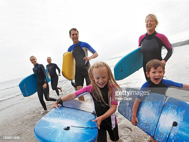 family running on beach with bodyboards