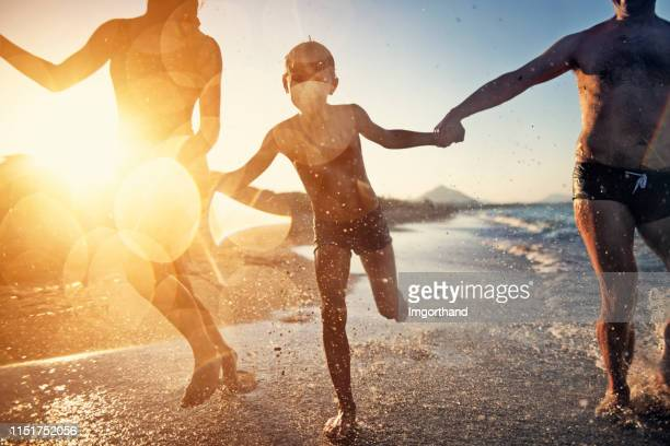 family running on the beach - summer stock pictures, royalty-free photos & images