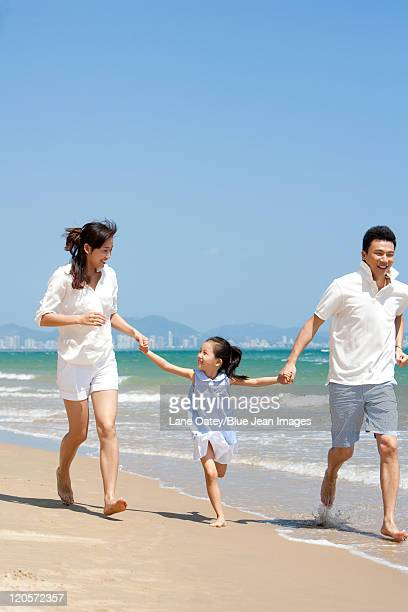 family running on the beach - wet t shirt girls stock photos and pictures
