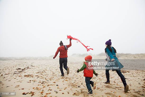 Family running on the beach with kite