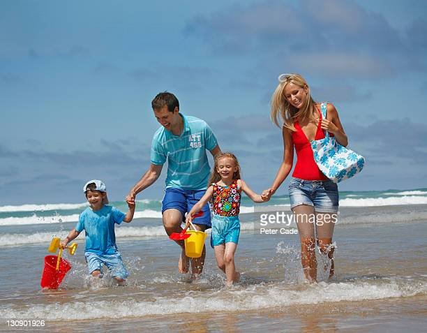 family running out of sea - cornwall england stock pictures, royalty-free photos & images