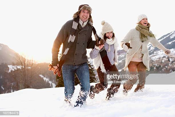 Family running outdoors in snow