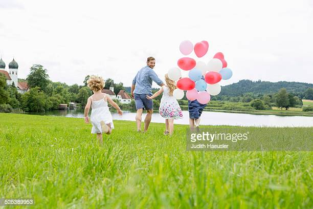 Family running through field with balloons