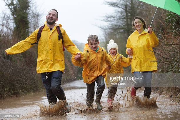 family running through muddy puddle - mother son shower stock photos and pictures